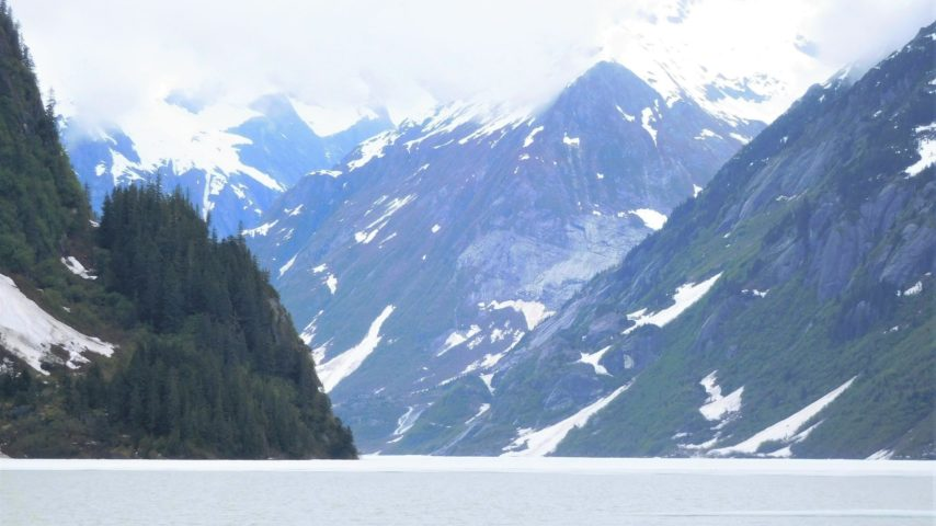 Nearing Shakes Glacier, narrow entrance, snow topped mountains, and ice on the water